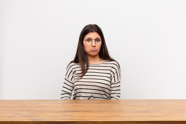 Jonge mooie vrouw verdrietig en gestrest voelen, boos vanwege een onaangename verrassing, met een negatieve, angstige blik zittend aan een tafel