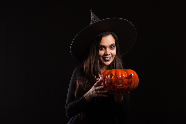 Jonge mooie vrouw verkleed als een heks voor halloween. jong met het houden van een pompoen. heks glimlachen.