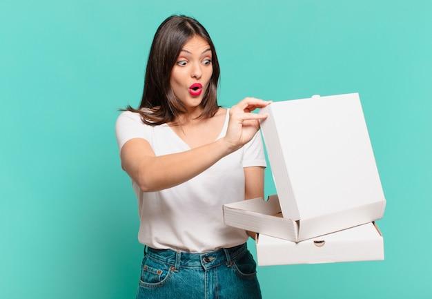 Jonge mooie vrouw verraste uitdrukking en houdt afhaalpizza's vast en houdt afhaalpizza's vast