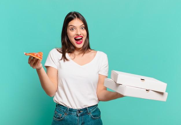 Jonge mooie vrouw verraste uitdrukking en houdt een pizza vast
