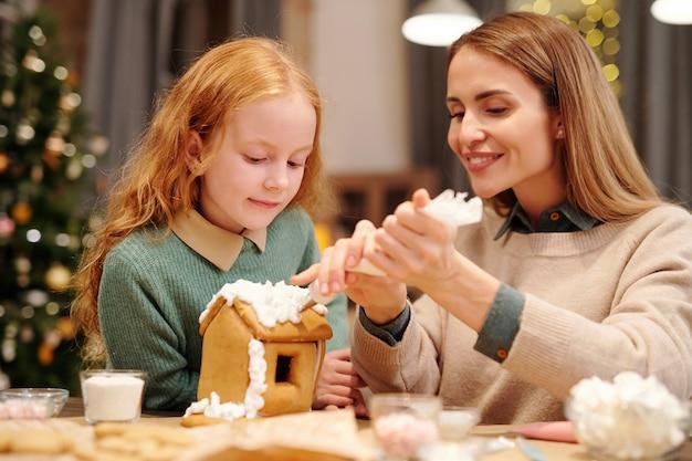 Jonge mooie vrouw versieren dak van zelfgemaakte peperkoek huis met slagroom terwijl ze dicht bij haar schattige dochter