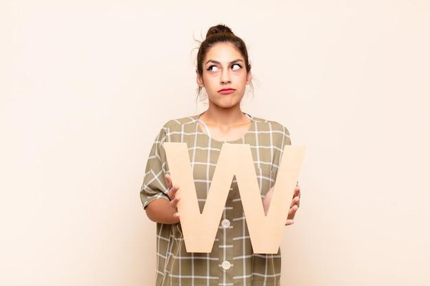 Jonge mooie vrouw verward, twijfelachtig, denkend, met de letter w van het alfabet om een woord of een zin te vormen.