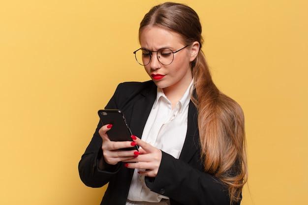 Jonge mooie vrouw verwarde uitdrukking slimme telefoon concept