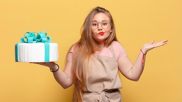 Jonge mooie vrouw verwarde uitdrukking verjaardagstaart concept