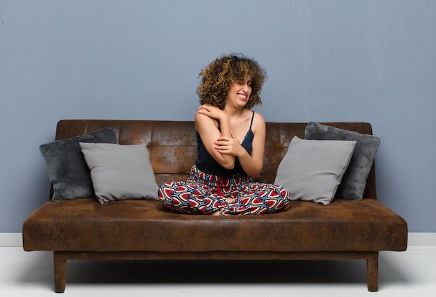 Jonge mooie vrouw voelt zich angstig, ziek, ziek en ongelukkig, lijdt aan een pijnlijke buikpijn of griep zittend op een bank.