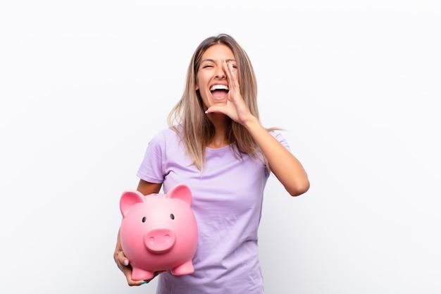 Jonge mooie vrouw voelt zich blij, opgewonden en positief, geeft een grote schreeuw met handen naast de mond, roept met een spaarvarken