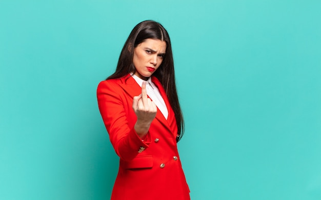 Jonge mooie vrouw voelt zich boos, geïrriteerd, opstandig en agressief, draait de middelvinger om en vecht terug. bedrijfsconcept