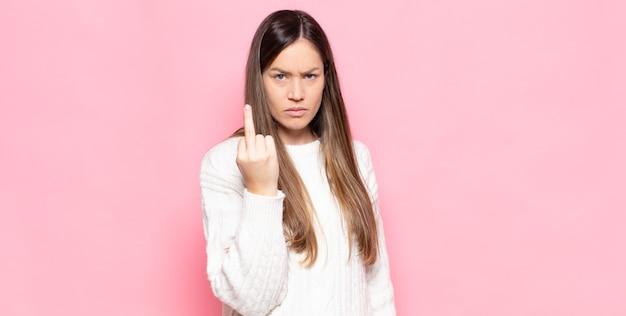 Jonge mooie vrouw voelt zich boos, geïrriteerd, opstandig en agressief, draait de middelvinger om en vecht terug