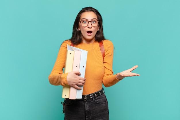Jonge mooie vrouw voelt zich extreem geschokt en verrast, angstig en in paniek, met een gestrest en geschokte blik. studentenconcept