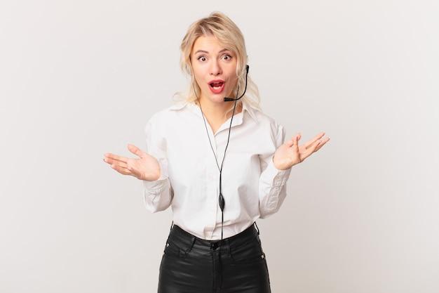 Jonge mooie vrouw voelt zich extreem geschokt en verrast. telemarketing concept
