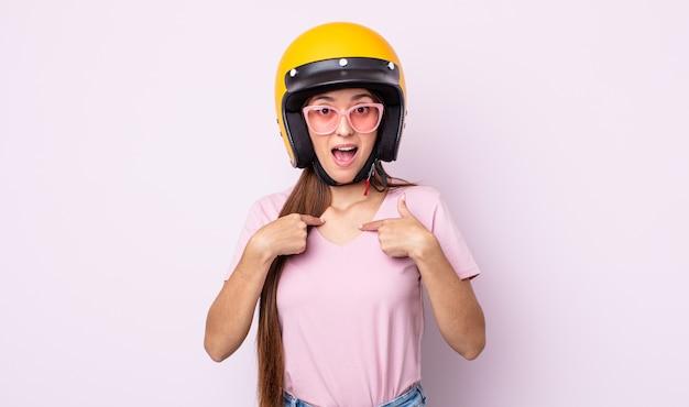 Jonge mooie vrouw voelt zich gelukkig en wijst naar zichzelf met een opgewonden. motorrijder en helm