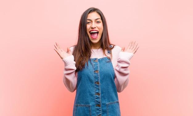 Jonge mooie vrouw voelt zich gelukkig, opgewonden, verrast of geschokt, glimlachend en verbaasd over iets ongelooflijks over de roze muur