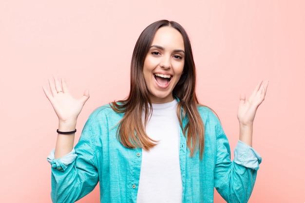 Jonge mooie vrouw voelt zich gelukkig, opgewonden, verrast of geschokt, glimlachend en verbaasd over iets ongelooflijks tegen de roze muur