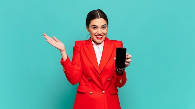 Jonge mooie vrouw voelt zich gelukkig, opgewonden, verrast of geschokt, glimlacht en verbaasd over iets ongelooflijks. slimme telefoon concept