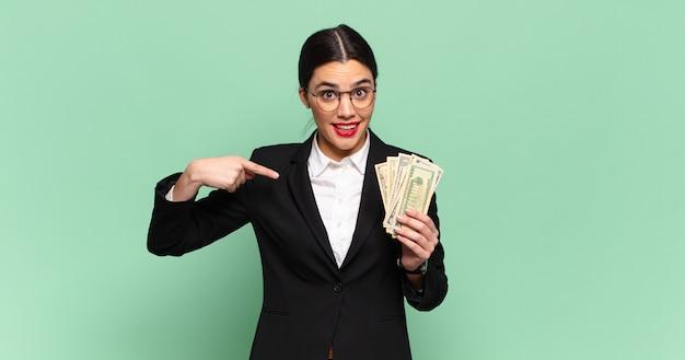 Jonge mooie vrouw voelt zich gelukkig, verrast en trots, wijzend naar zichzelf met een opgewonden, verbaasde blik. bedrijfs- en bankbiljettenconcept