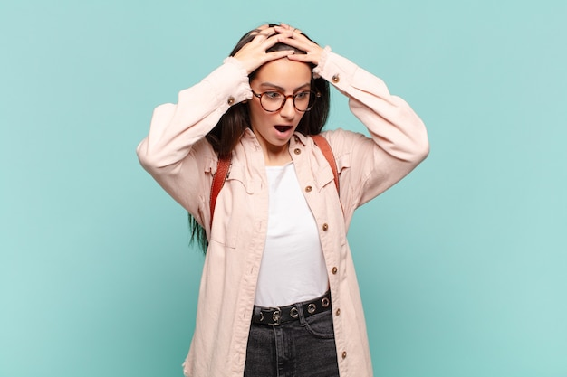 Jonge mooie vrouw voelt zich geschokt en geschokt, steekt handen tegen het hoofd en raakt in paniek bij een fout. studentenconcept
