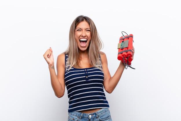 Jonge mooie vrouw voelt zich geschokt, opgewonden en gelukkig, lacht en viert succes en zegt wow! met een dynamietbom