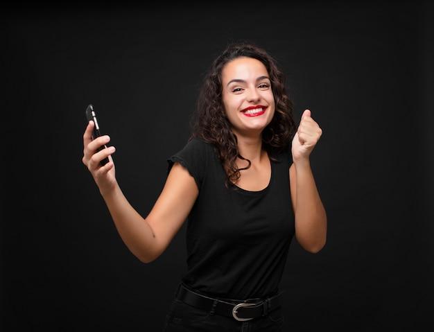 Jonge mooie vrouw voelt zich geschokt, opgewonden en gelukkig, lacht en viert succes en zegt wow! met een smartphone