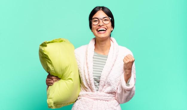 Jonge mooie vrouw voelt zich geschokt, opgewonden en gelukkig, lacht en viert succes en zegt wow!. pyjama concept