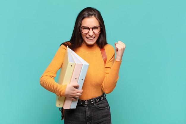 Jonge mooie vrouw voelt zich geschokt, opgewonden en gelukkig, lacht en viert succes en zegt wow!. studentenconcept