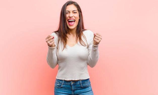 Jonge mooie vrouw voelt zich geschokt, opgewonden en gelukkig, lacht en viert succes en zegt wow! tegen roze muur.