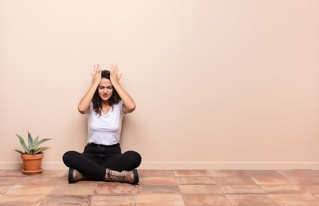 Jonge mooie vrouw voelt zich gestrest en angstig, depressief en gefrustreerd met hoofdpijn, beide handen opheffend om een terrasvloer te zitten