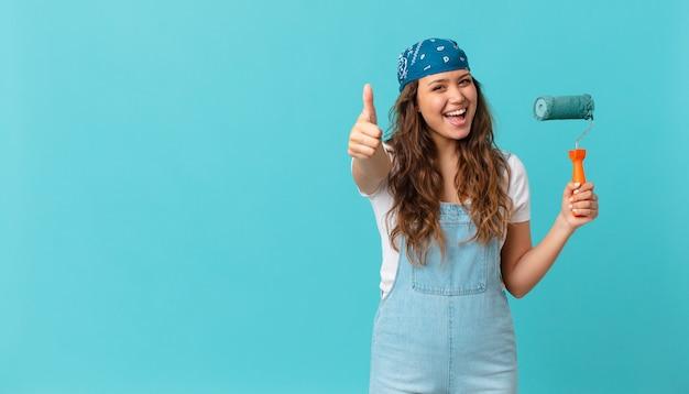 Jonge mooie vrouw voelt zich trots, lacht positief met duimen omhoog en schildert een muur