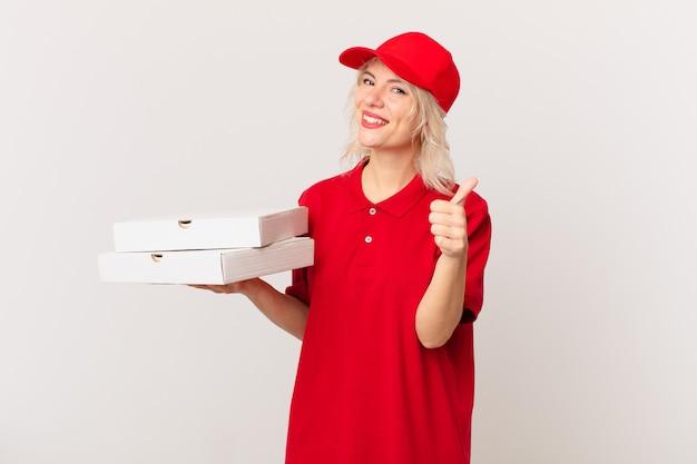 Jonge mooie vrouw voelt zich trots, positief glimlachend met duimen omhoog. pizza bezorgconcept