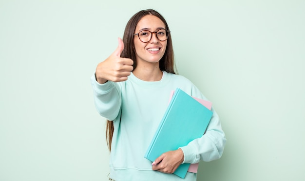 Jonge mooie vrouw voelt zich trots, positief glimlachend met duimen omhoog. universitaire student