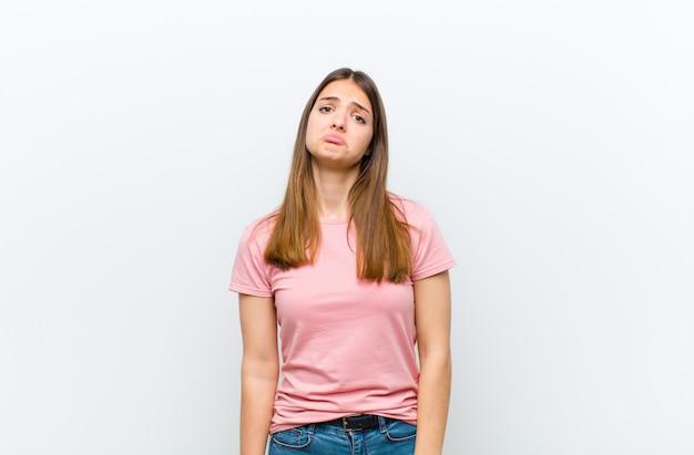 Jonge mooie vrouw voelt zich verdrietig en zeurderig met een ongelukkige blik, huilend met een negatieve en gefrustreerde houding over witte muur