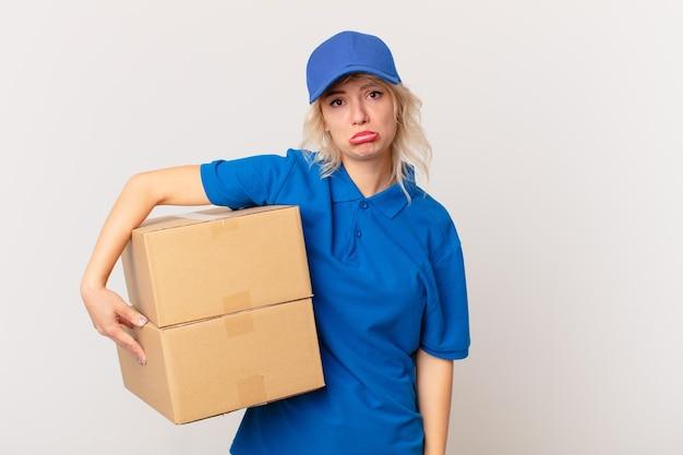 Jonge mooie vrouw voelt zich verdrietig en zeurt met een ongelukkige blik en huilt. pakket leveren concept