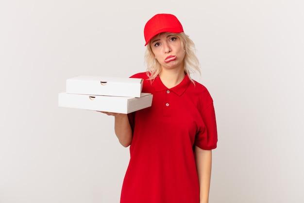 Jonge mooie vrouw voelt zich verdrietig en zeurt met een ongelukkige blik en huilt. pizza bezorgconcept