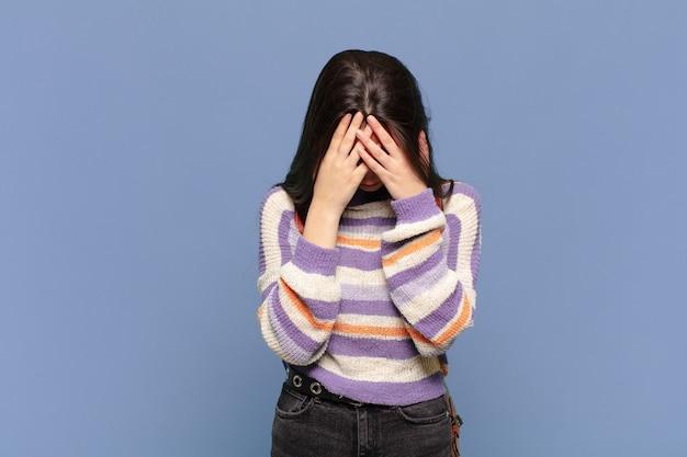 Jonge mooie vrouw voelt zich verdrietig, gefrustreerd, nerveus en depressief, bedekt gezicht met beide handen, huilend. studentenconcept