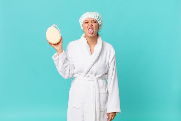 Jonge mooie vrouw voelt zich walgelijk en geïrriteerd en tong uit en draagt een badjas na het douchen