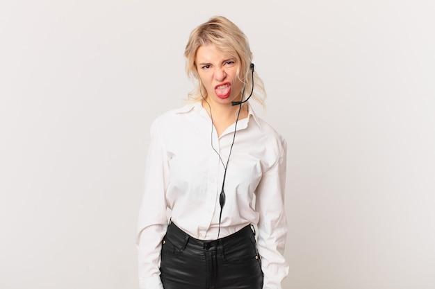 Jonge mooie vrouw voelt zich walgelijk en geïrriteerd en tong uit. telemarketing concept