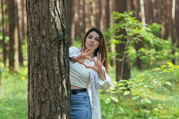 Jonge mooie vrouw vrijwilliger in het bos in de buurt van een glimlachende boom kijkt naar de camera en toont handen en vingers een hart een teken van liefde voor de natuur