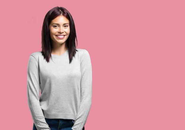 Jonge mooie vrouw, vrolijk en met een grote glimlach, zelfverzekerd, vriendelijk en oprecht, positiviteit en succes uitdrukken