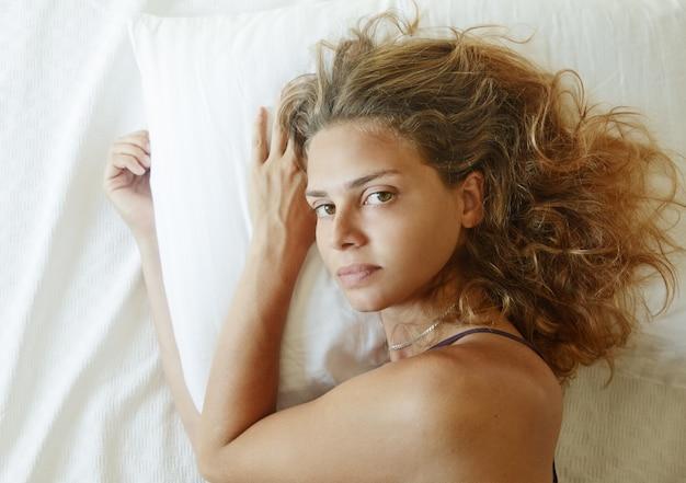 Jonge mooie vrouw wakker in bed, close-up portret