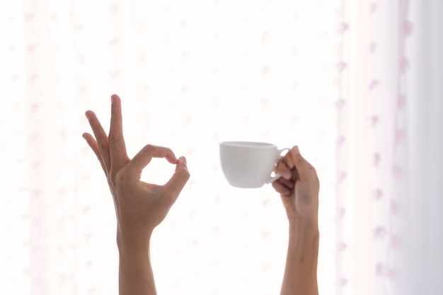 Jonge mooie vrouw wakker in de ochtend in het bed, strekt zijn armen met een kopje koffie en toont ok teken.