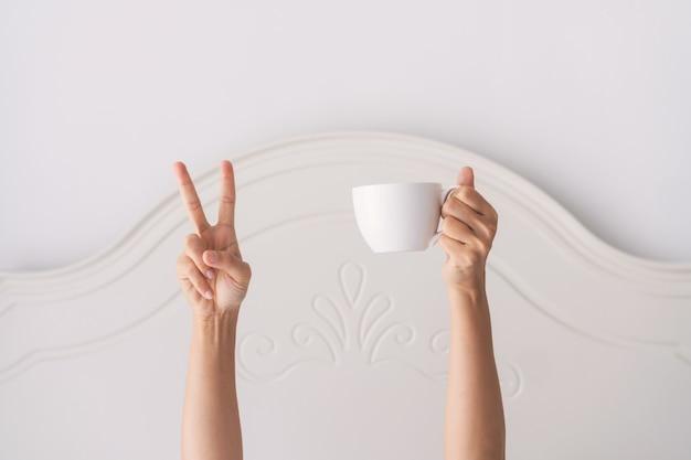 Jonge mooie vrouw wakker in de ochtend in het bed, verstopt onder de deken, strekt zijn armen met een kopje koffie en toont v-teken.