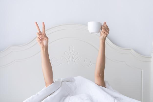 Jonge mooie vrouw wakker in de ochtend in het bed, verstopt onder de deken, strekt zijn armen uit met een kopje koffie en toont v-teken.
