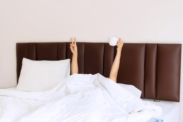 Jonge mooie vrouw wakker in de ochtend in het bed