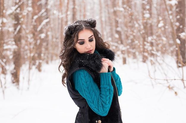 Jonge mooie vrouw wandelen in besneeuwde park