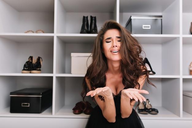 Jonge mooie vrouw weet niet wat ze moet dragen, moeilijk om een keuze te maken, staat in de kleedkamer.