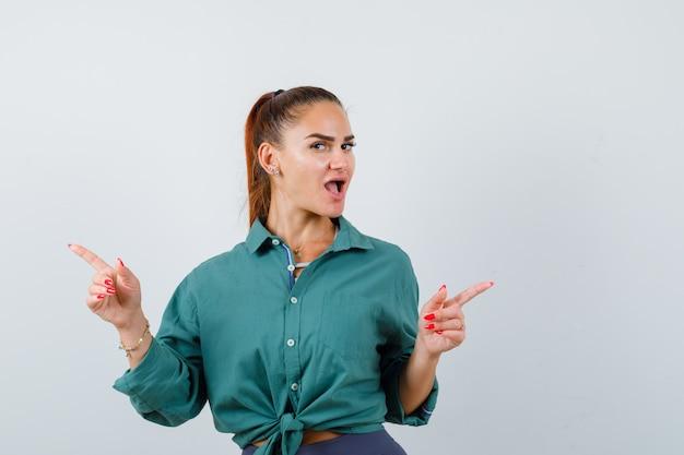 Jonge mooie vrouw wijst naar tegenovergestelde richtingen in groen shirt en kijkt verbijsterd, vooraanzicht.