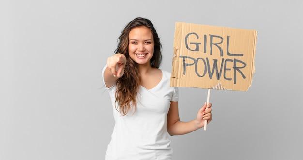 Jonge mooie vrouw wijzend op de camera die jou kiest en een girl power banner vasthoudt