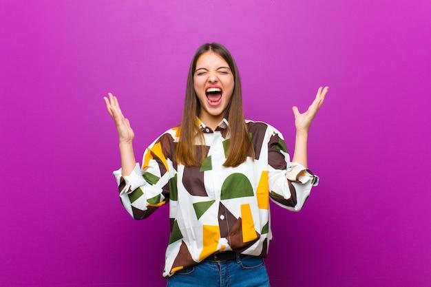 Jonge mooie vrouw woedend schreeuwen, gestrest en geïrriteerd voelen met handen omhoog in de lucht en zeggen waarom ik over paarse muur