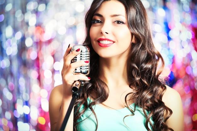 Jonge mooie vrouw zingen op lichte achtergrond