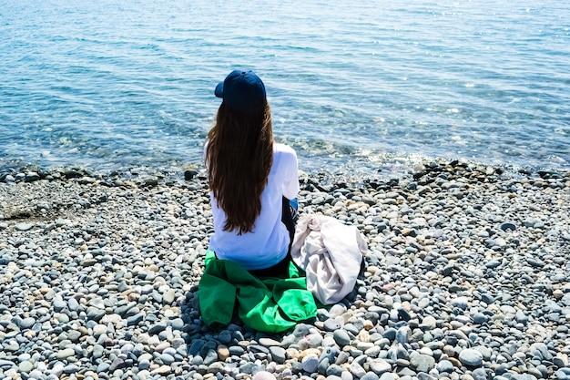 Jonge mooie vrouw zit met haar rug naar de camera kijken naar de zee