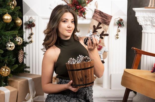 Jonge mooie vrouw zit met mand met dennenappels in de buurt van de kerstboom